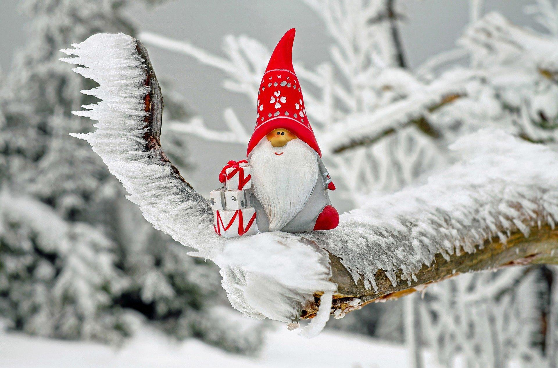 Weihnachtsmann-Figur auf verschneitem Ast